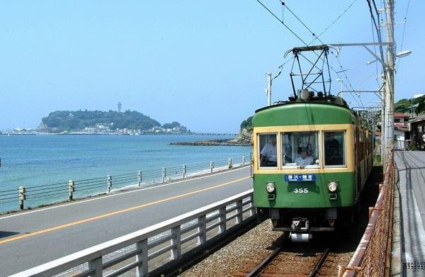 鎌倉方面へ向かう江ノ電。江の島と一緒に撮影できるこの場所は鉄道ファンの人気が高い=神奈川県鎌倉市
